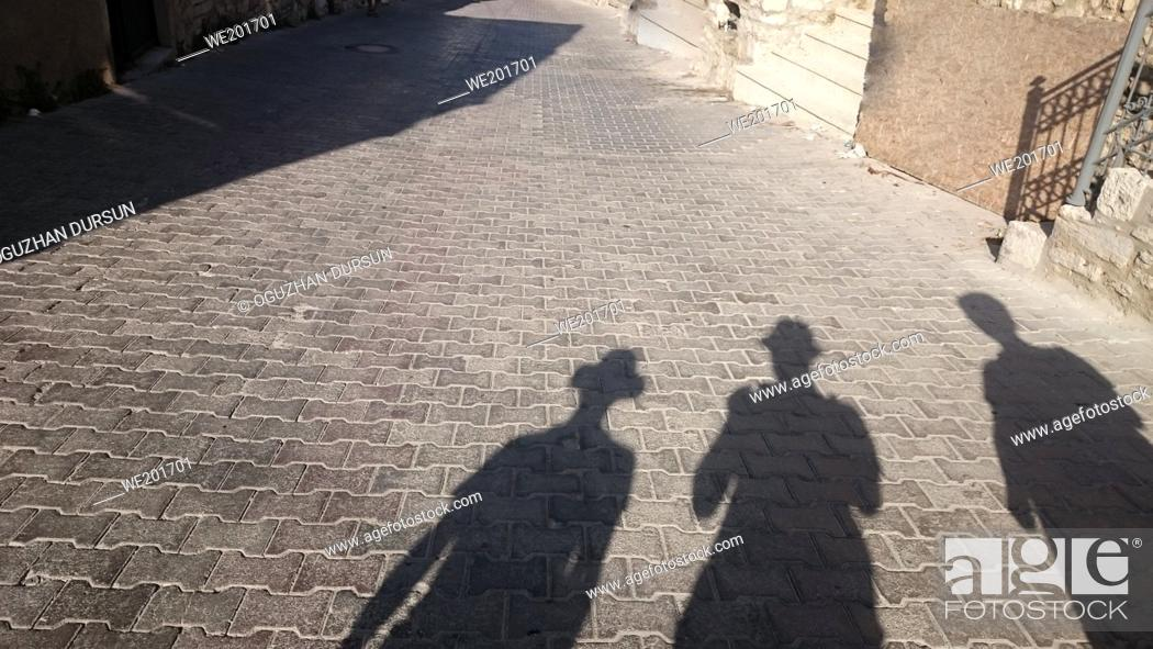 Stock Photo: Shadow of three people on the ground in the city with copy space.