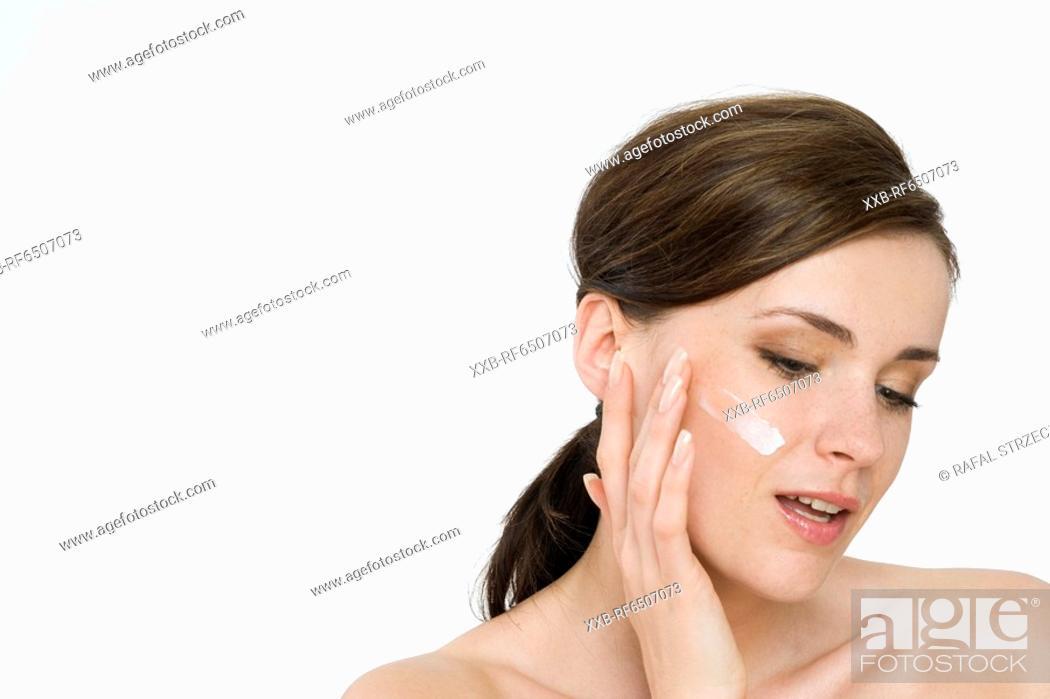 Stock Photo: woman creaming face.
