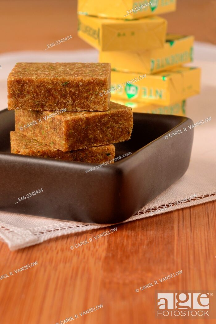 Stock Photo: Bouillon blocks stacked in a small black dish. Lower point of view with stack of bouillon cubes in foil wrappers in the background.