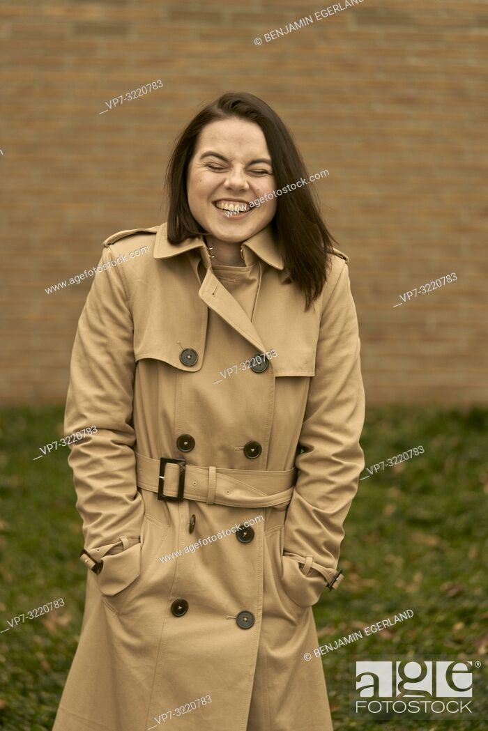 Stock Photo: young happy laughing woman outdoors in city park during autumn season, wearing coat, candid emotion, closed eyes, pure happiness, in Munich, Bavaria, Germany.