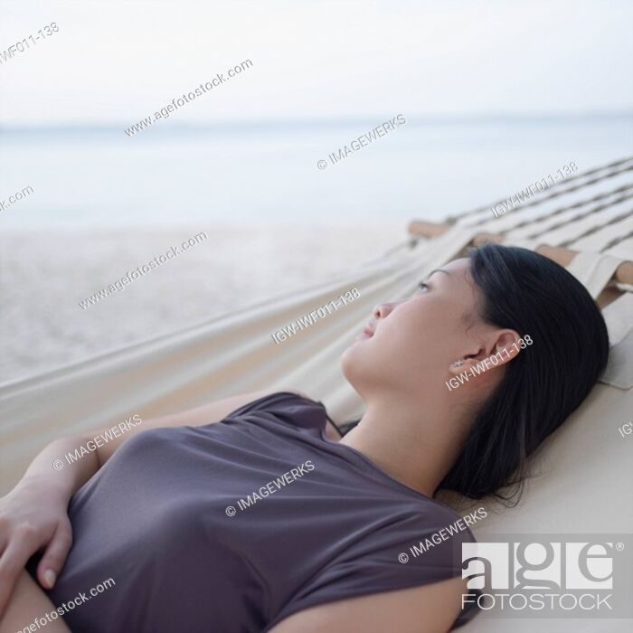 Stock Photo: Side profile of a young woman relaxing in a hammock.