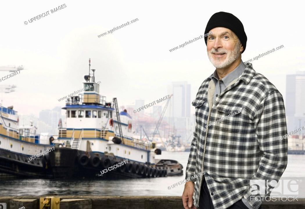 Stock Photo: Senior male fisherman in front of fishing boat.