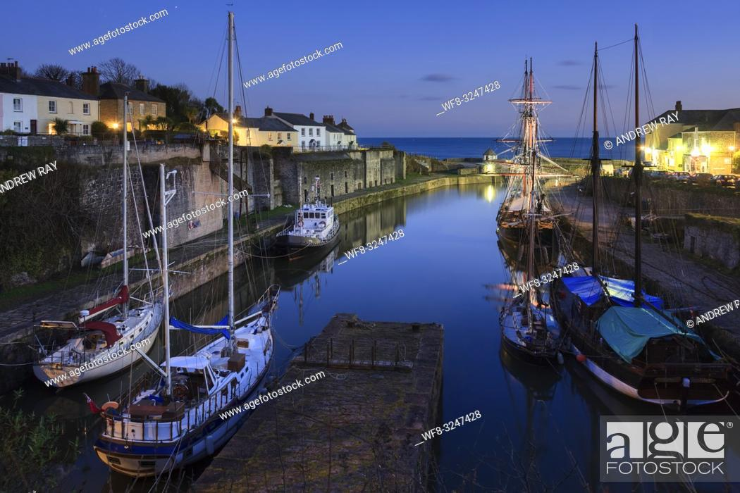 Stock Photo: The resident tall ships in the Georgian port of Charlestown on the south coast of Cornwall, captured during twilight on an evening in mid January.