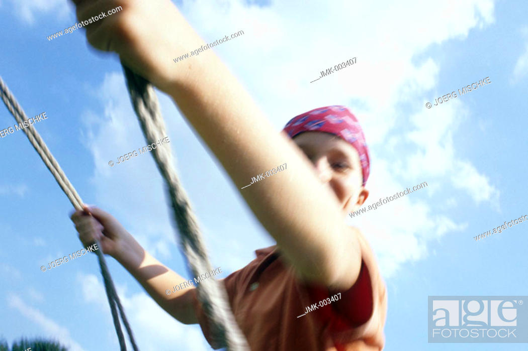 Stock Photo: A boy, 5-10 years old, swinging outside in the garden in summer.
