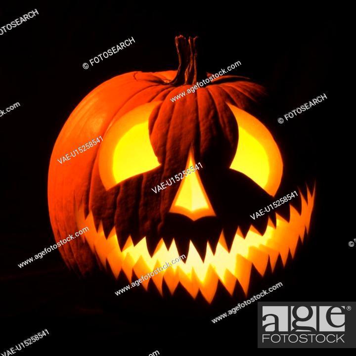 Stock Photo: Carved Halloween pumpkin glowing in the dark.