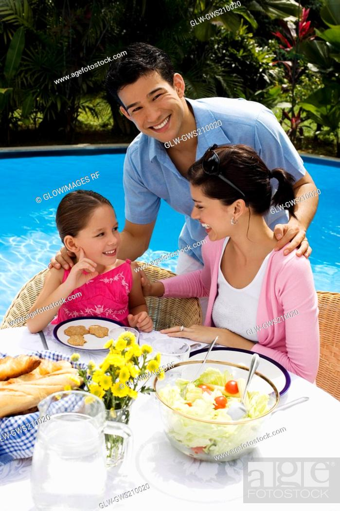 Stock Photo: Young couple with their daughter at a breakfast table.