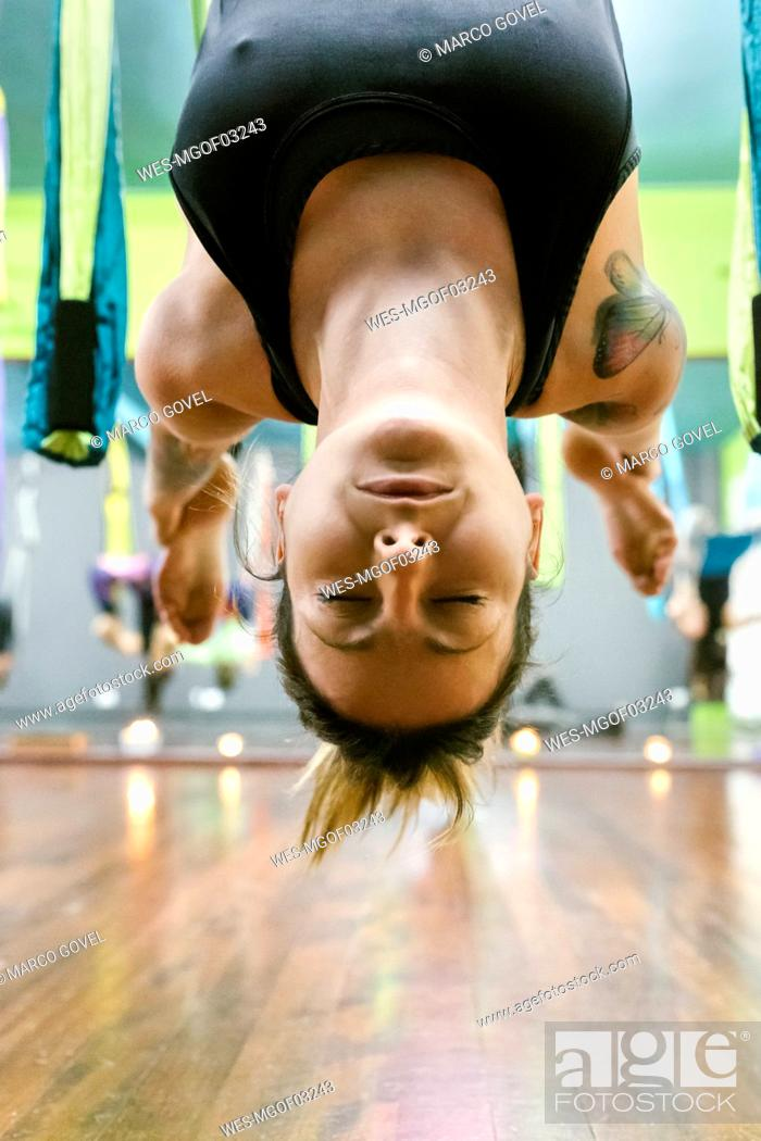 Stock Photo: Woman practicing aerial yoga in class.