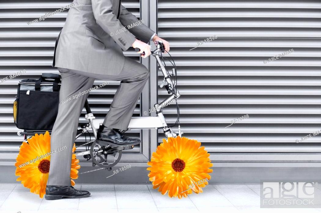 Stock Photo: Businessman riding bike with flower wheels.