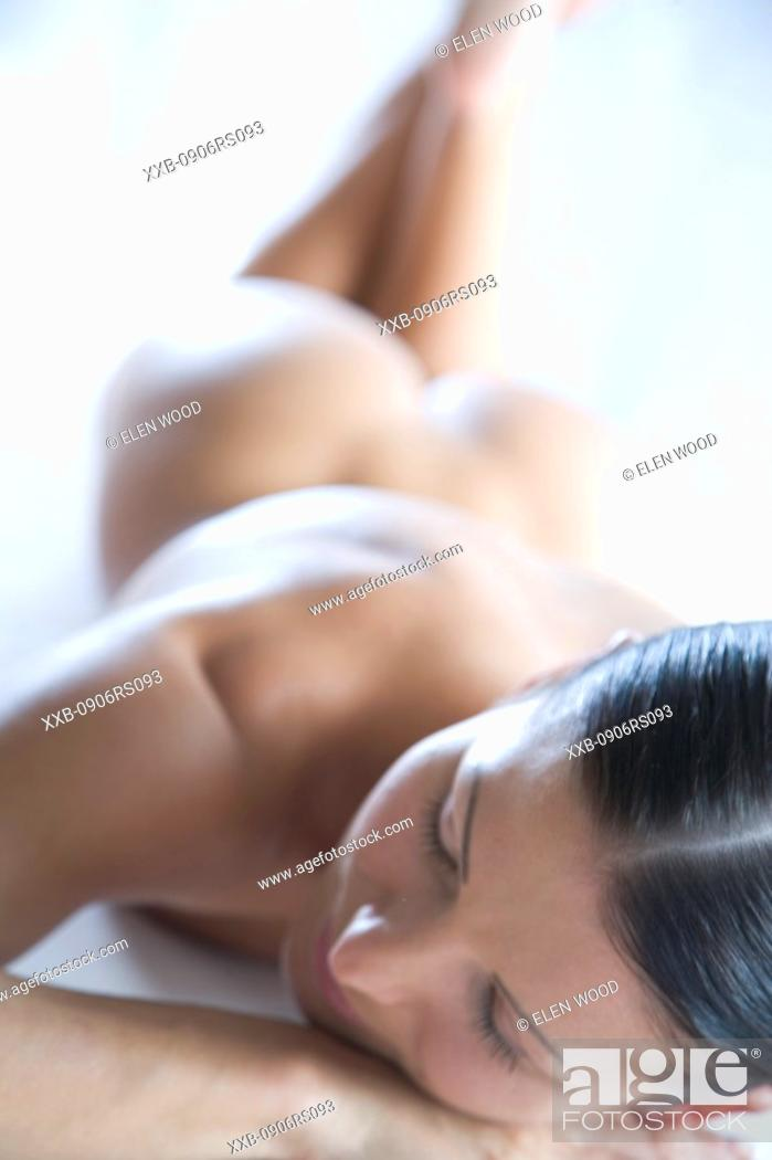 Stock Photo: nude woman laying on stomach.