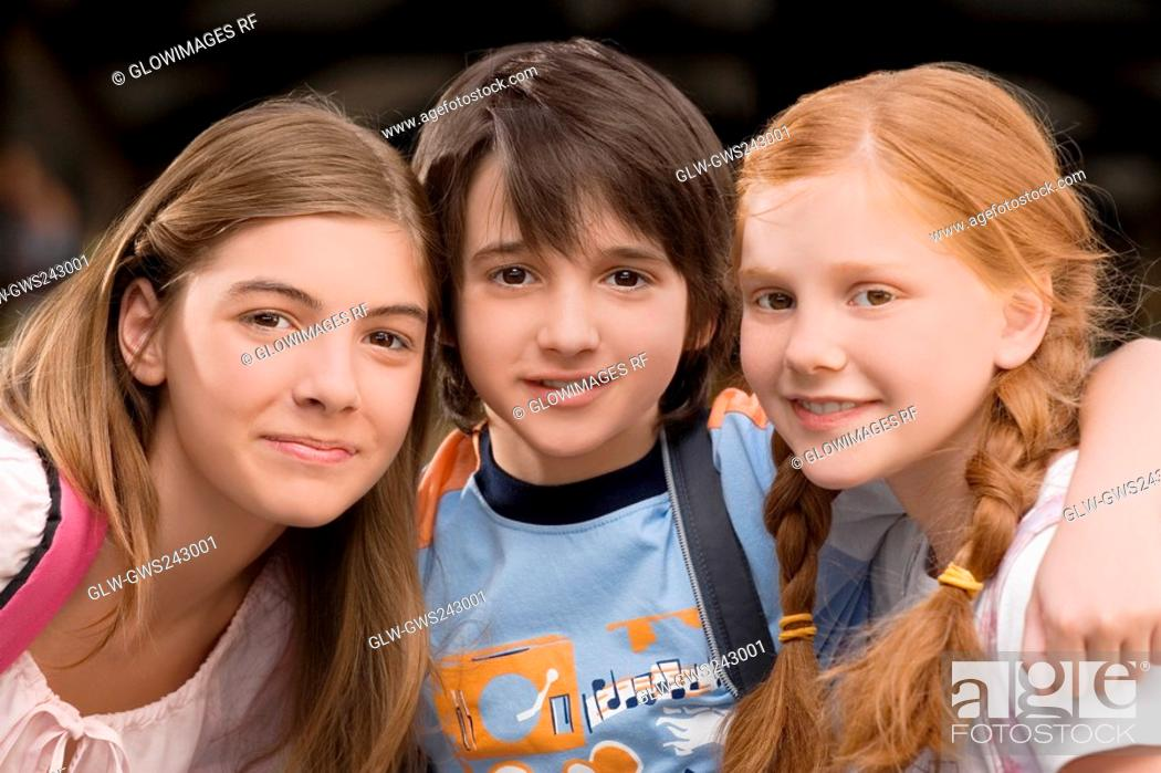 Stock Photo: Portrait of a schoolboy with two schoolgirls smiling together.