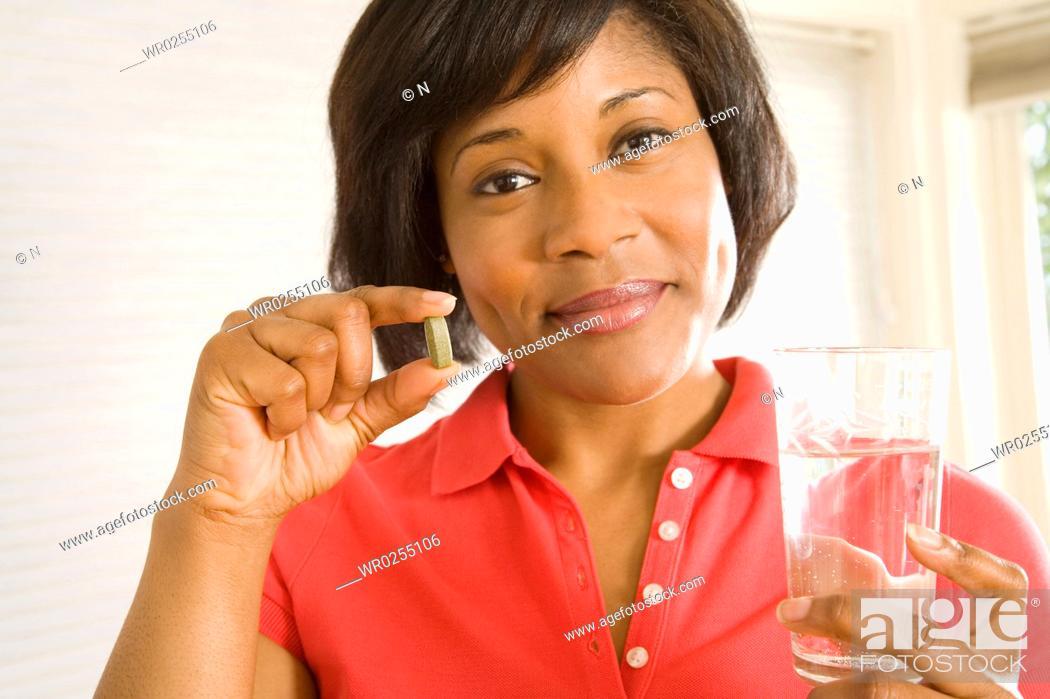 Stock Photo: Woman taking a pill.