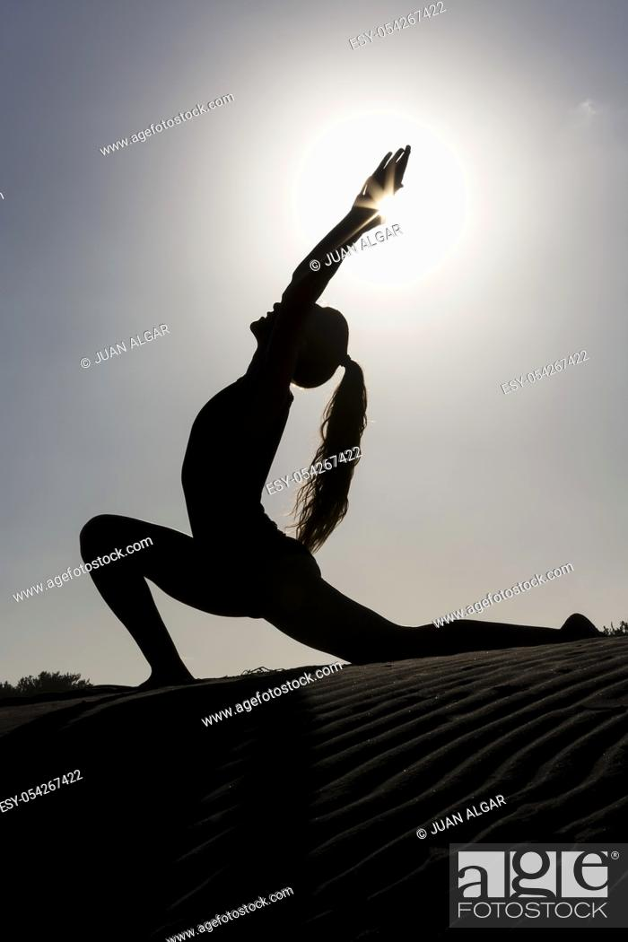 Stock Photo: Side view of black silhouette of woman on sandy beach doing asana in back lit.