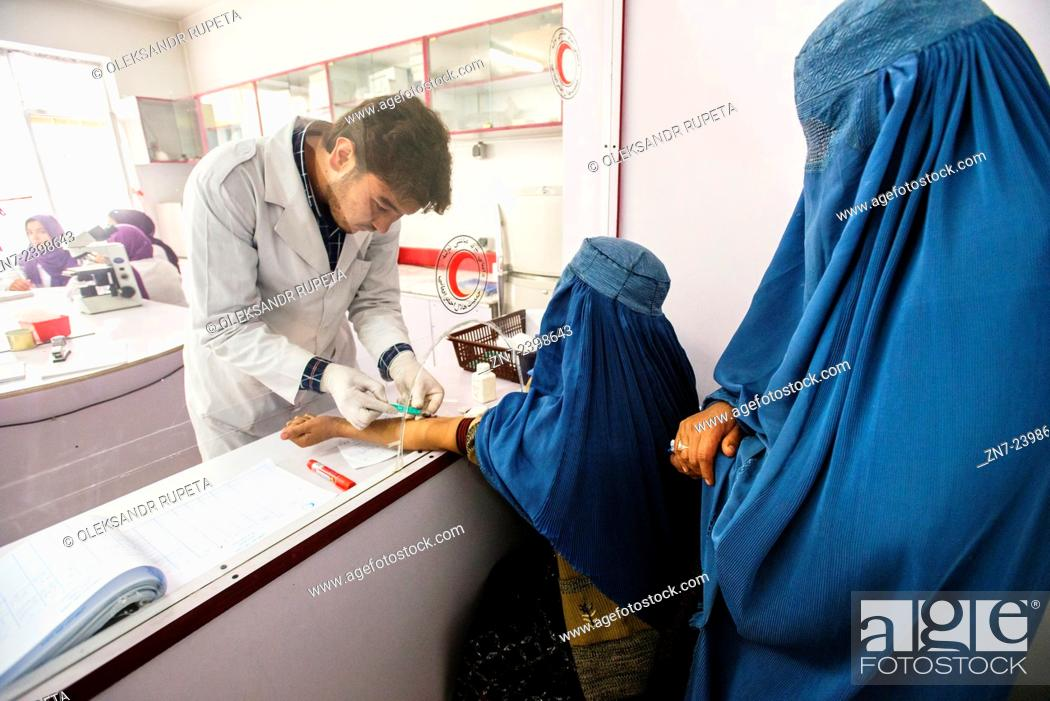Stock Photo: Laboratory staff draws blood of woman wearing burka for blood test in laboratory of Central Hospital of Afghan Red Crescent Society, Kabul, Afghanistan.