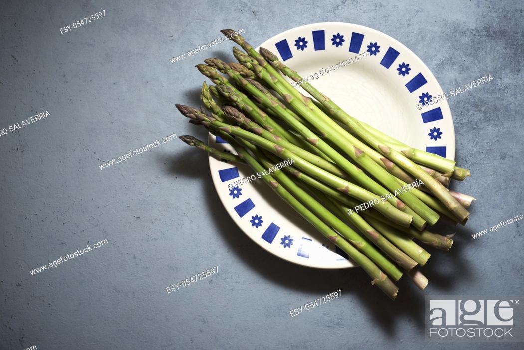Stock Photo: Wild asparagus on a gray table.