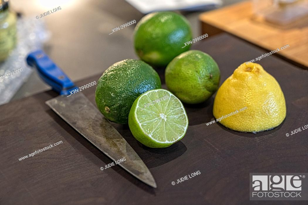 Imagen: Lemons and Limes, Two Cut in Half, on a Cutting Board, Knife on the Side. NYC.
