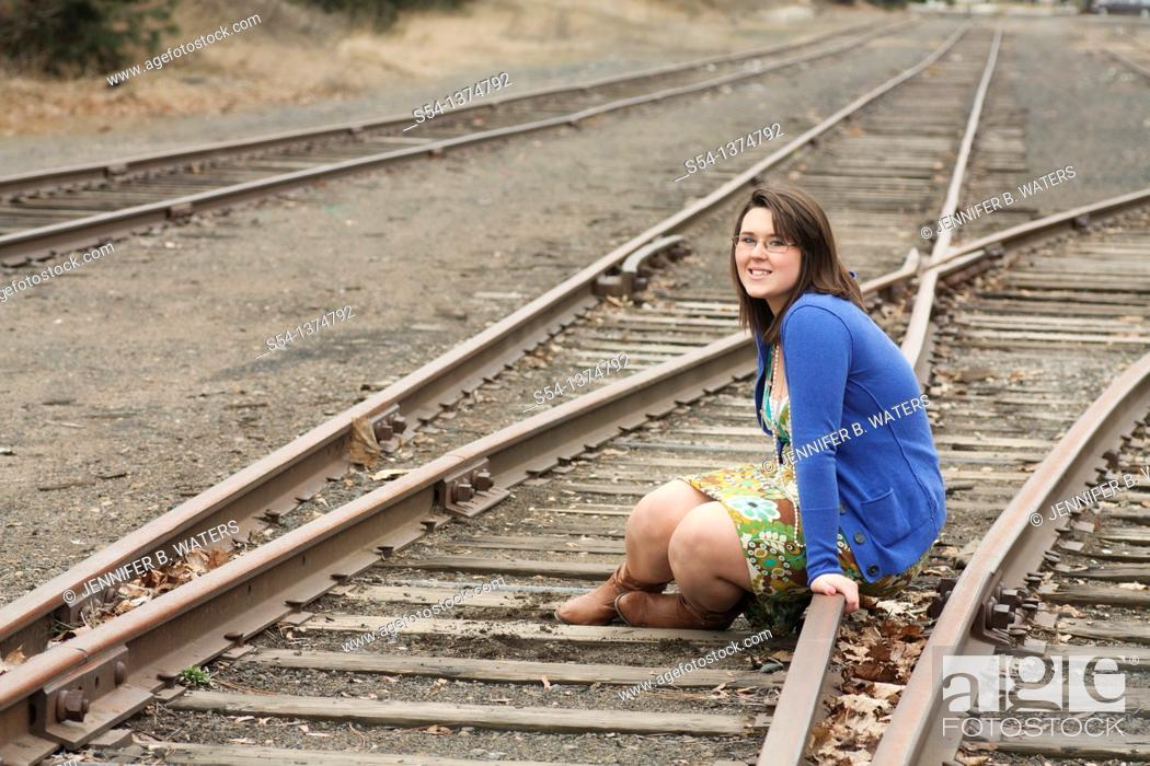 Stock Photo: A happy young woman sitting on train tracks outdoors.
