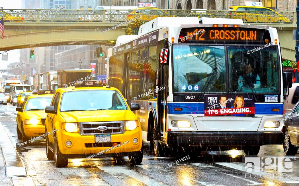 Stock Photo: Mass Transit on Pershing Square, M42 MTA Crosstown Bus, outside Grand Central Terminal, morning rush hour during a snow and rain storm, Madison Avenue.