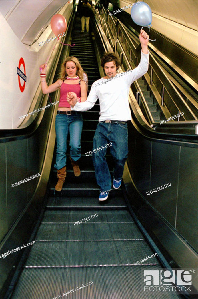 Stock Photo: Couple with balloons on escalator.