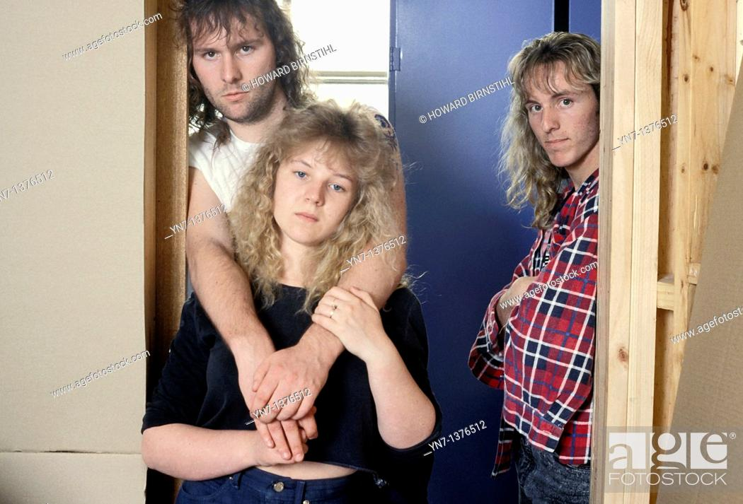 Stock Photo: three rather sullen teenagers lounge together in an interior doorway.