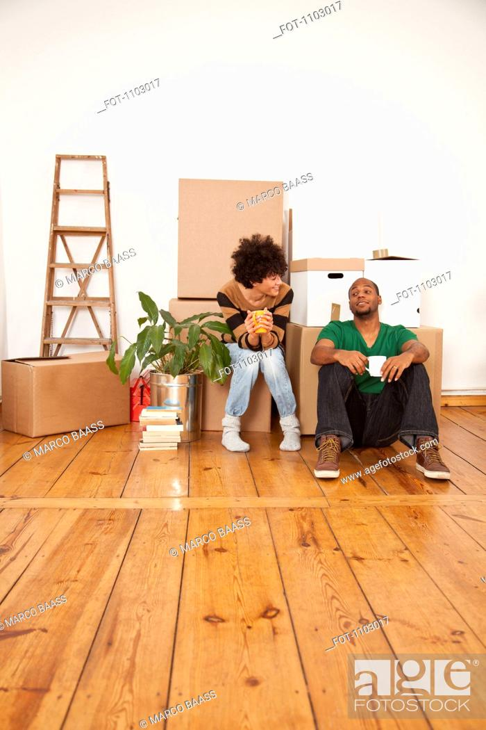 Stock Photo: A cheerful couple taking a coffee break while moving house.