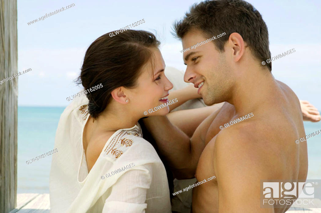 Stock Photo: Close-up of a young couple lying on a pier and looking at each other.