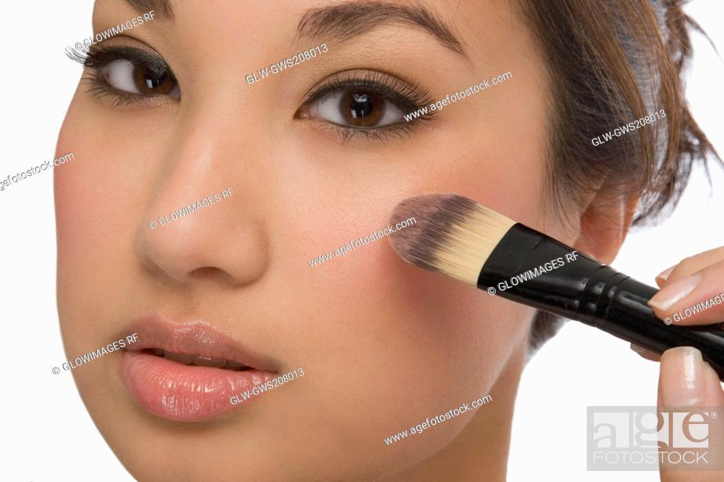 Stock Photo: Portrait of a young woman applying make-up.