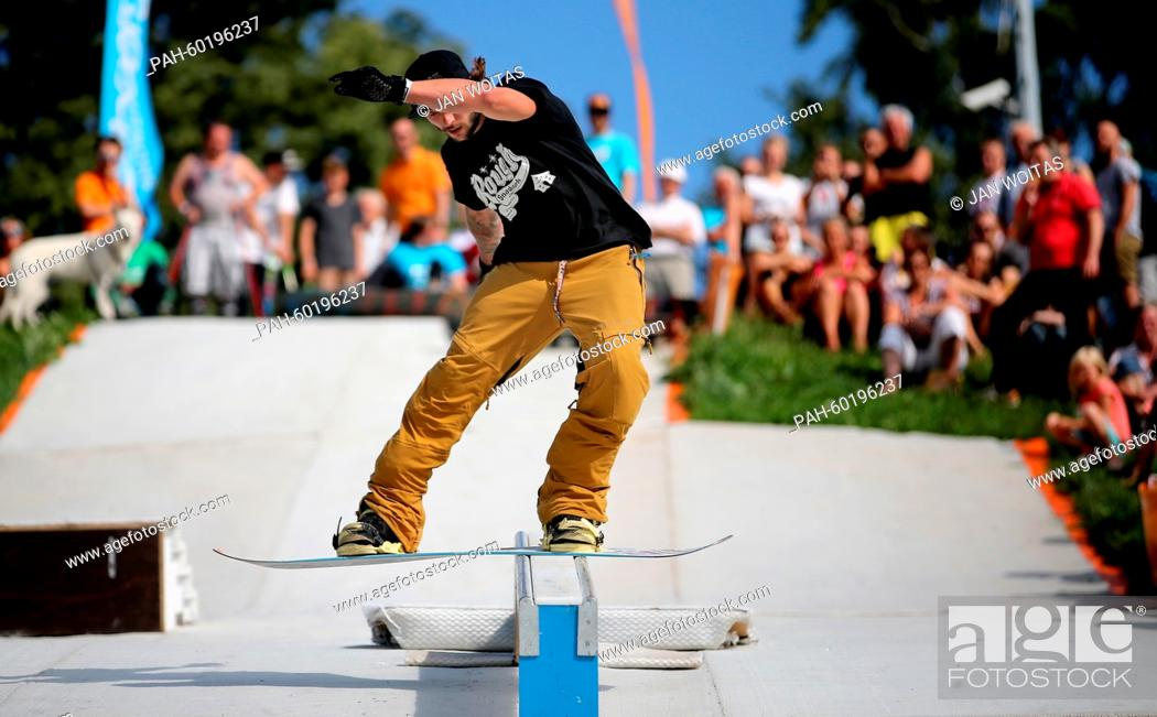 Stock Photo: Marcel Wolfram traverses a rail with his snowboard in Augustusburg, Germany, 19 July 2015. More than 20 sportsman have come to the hillside to show of their.