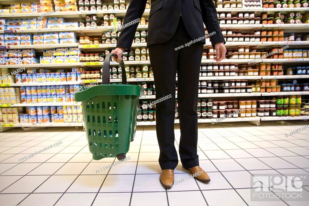 Stock Photo: Shopper with shopping basket standing in supermarket aisle.