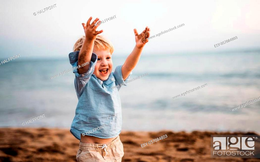 Stock Photo: A cheerful small toddler boy standing on beach on summer holiday, having fun.