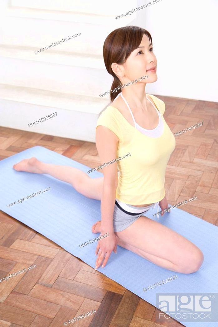 Stock Photo: Young woman doing yoga exercise, stretching, high angle view.