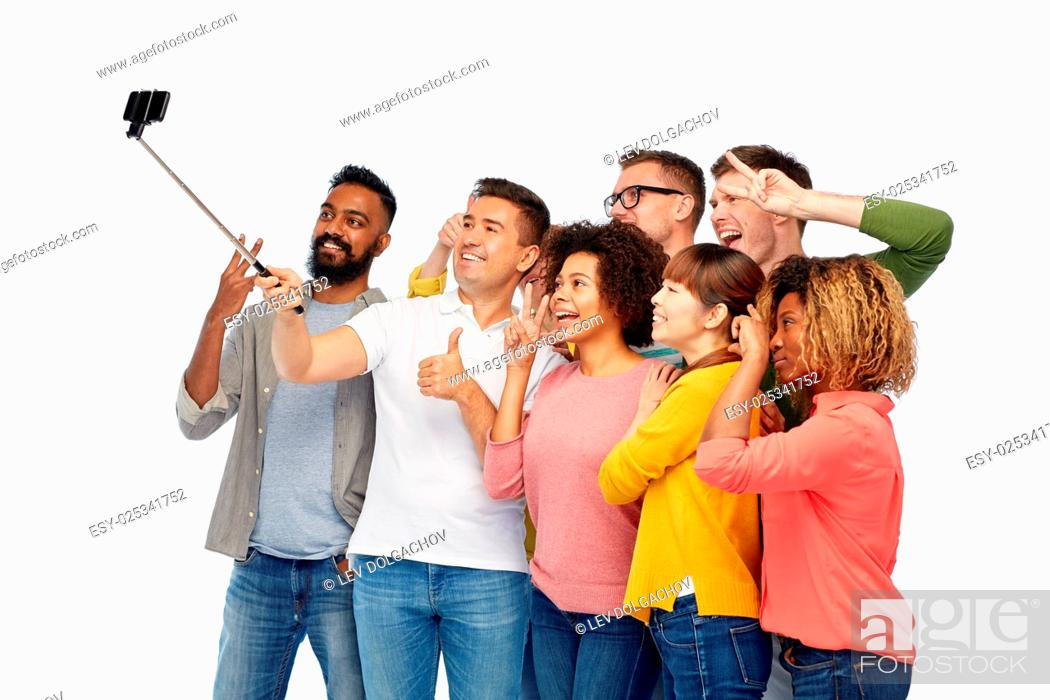 Stock Photo: diversity, race, ethnicity, technology and people concept - international group of happy smiling men and women taking picture by smartphone selfie stick over.