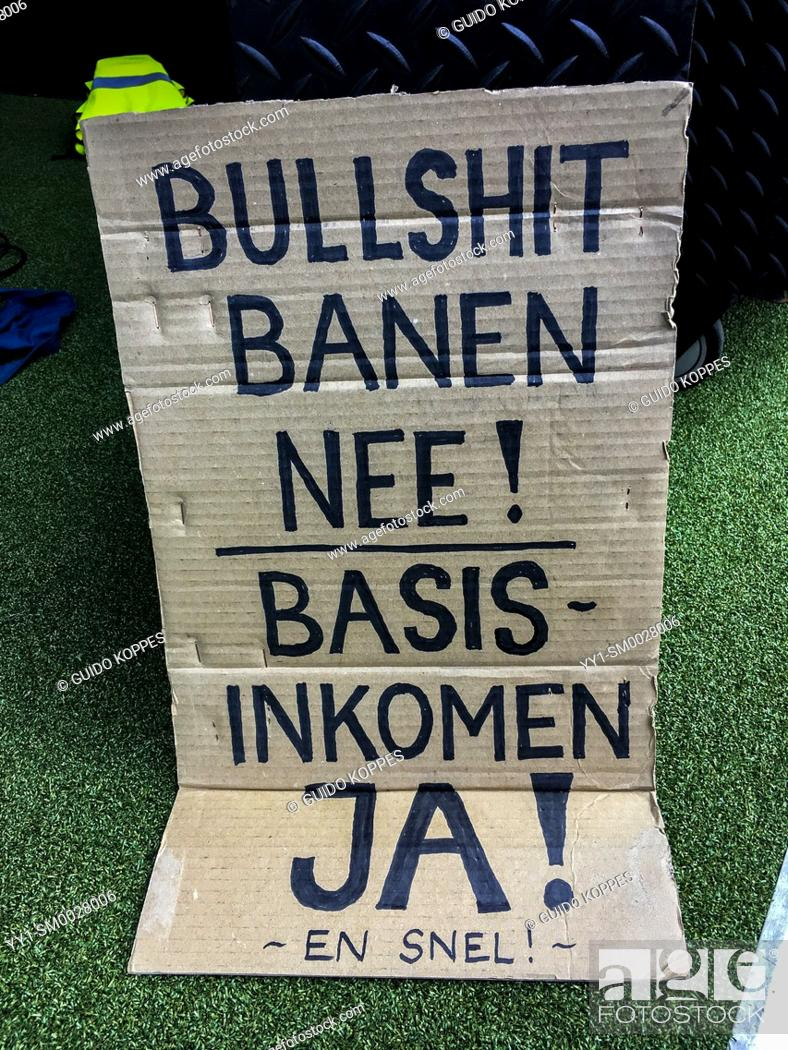 Stock Photo: Amsterdam, Netherlands. Basic Income Demonstration Sign against dead end jobs and in favour of Basic Income for all.