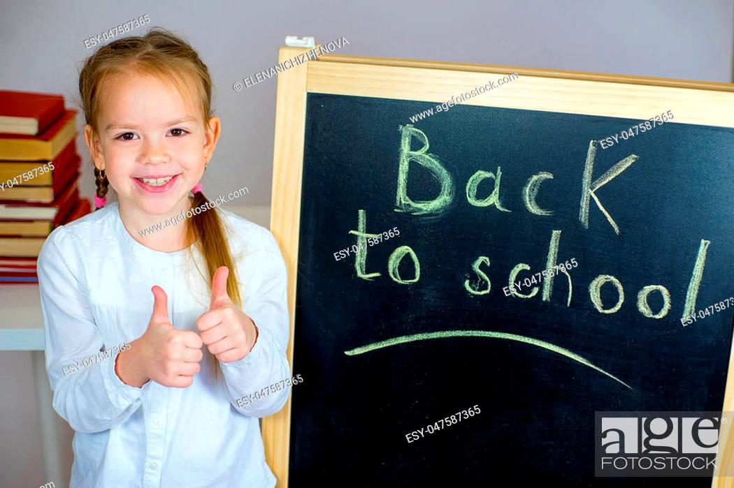 Stock Photo: young schoolgirl with schoolbag near the blackboard. thumbs up. isolated on grey background.