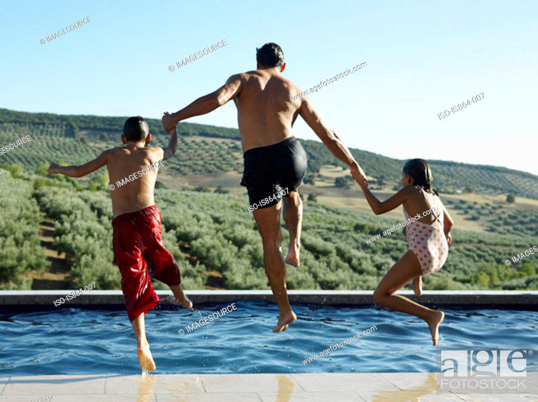 Stock Photo: Father and children jumping into pool.