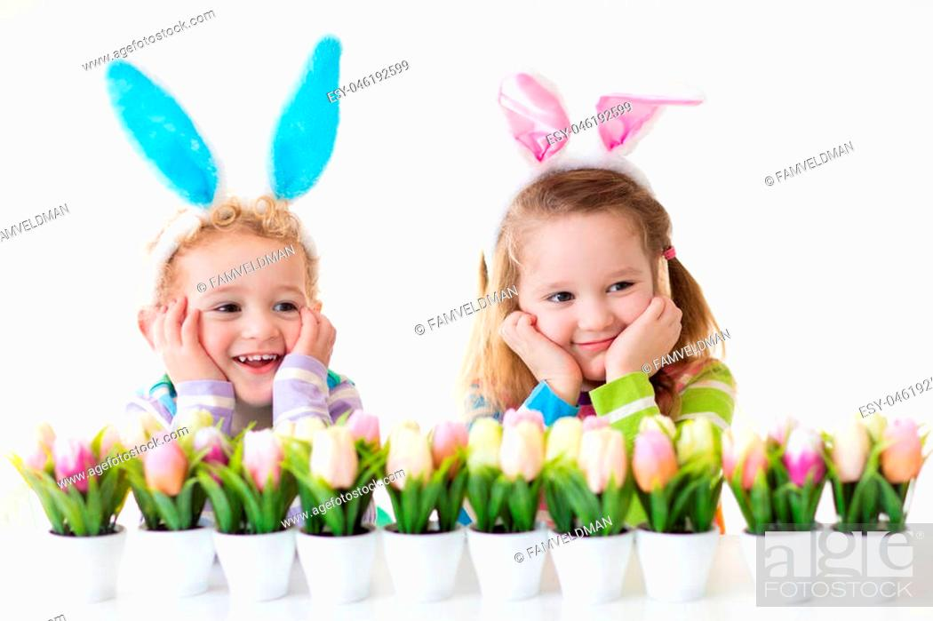 Stock Photo: Happy children celebrate Easter at home. Boy and girl wearing bunny ears enjoying egg hunt. Kids playing with color eggs and flower basket.