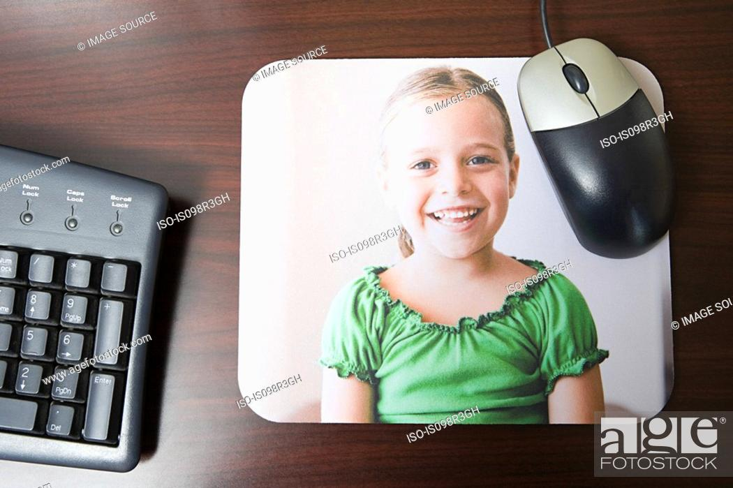 Stock Photo: Personalised mousepad with photo of little girl on it.