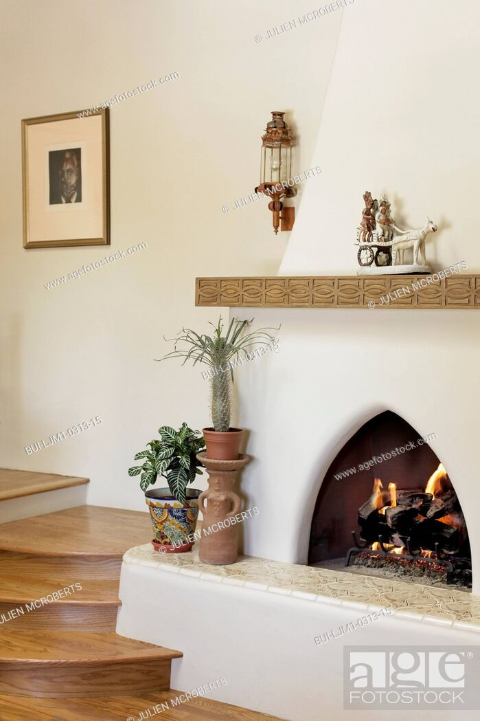 Imagen: Lit fireplace with wooden stairs at home; Santa Fe; New Mexico; USA.