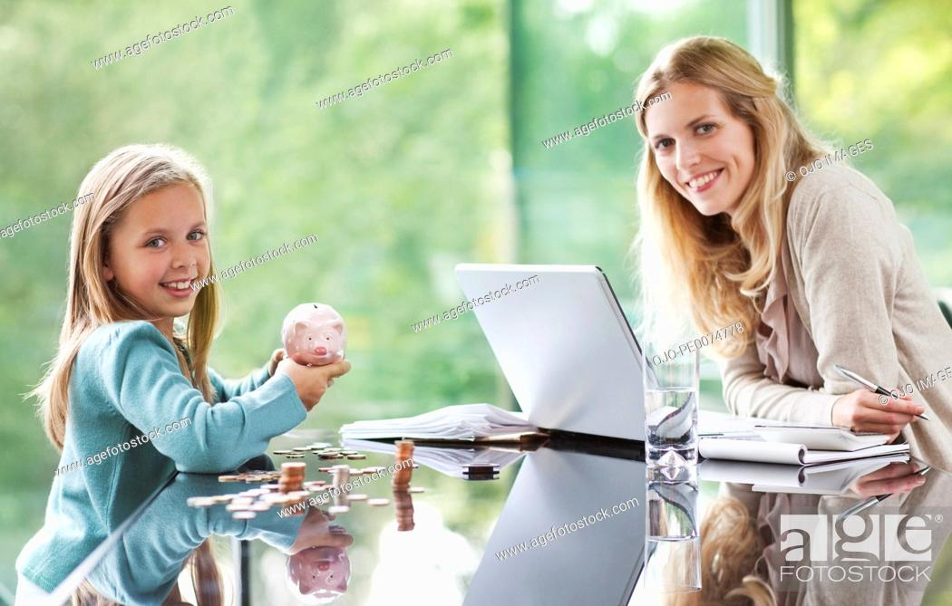 Stock Photo: Mother watching daughter count coins from piggy bank.