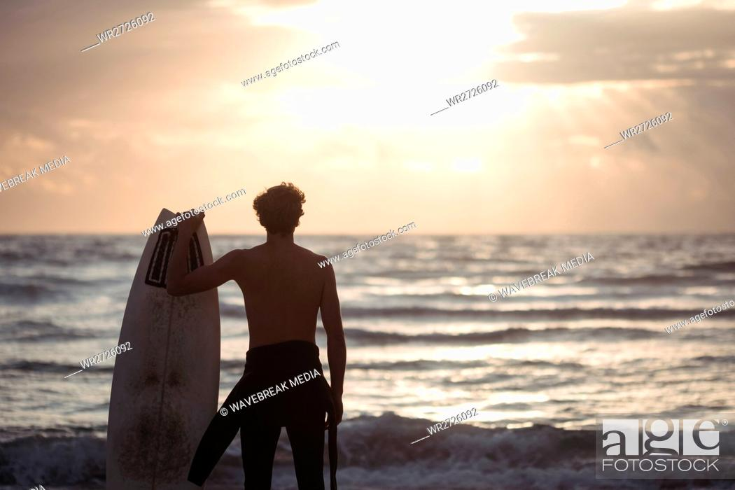 Stock Photo: Man carrying surfboard standing on beach.
