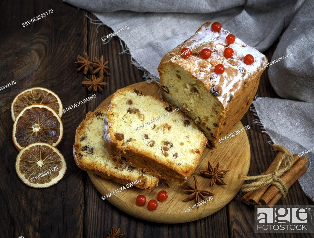 Stock Photo: baked big cake with dried fruit and cut into slices on a wooden board, top view.