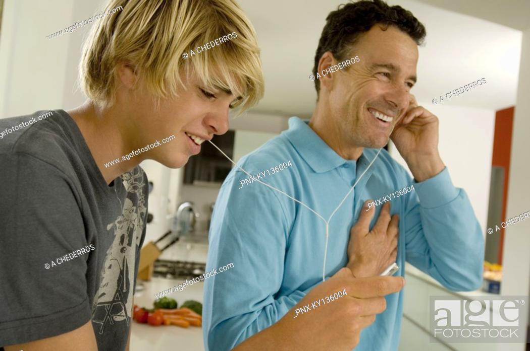 Stock Photo: Father and son listening to music with MP3 player, indoors.