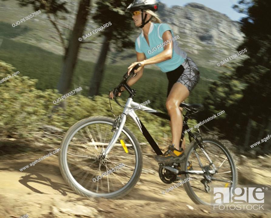 Stock Photo: A woman biking on a trail.