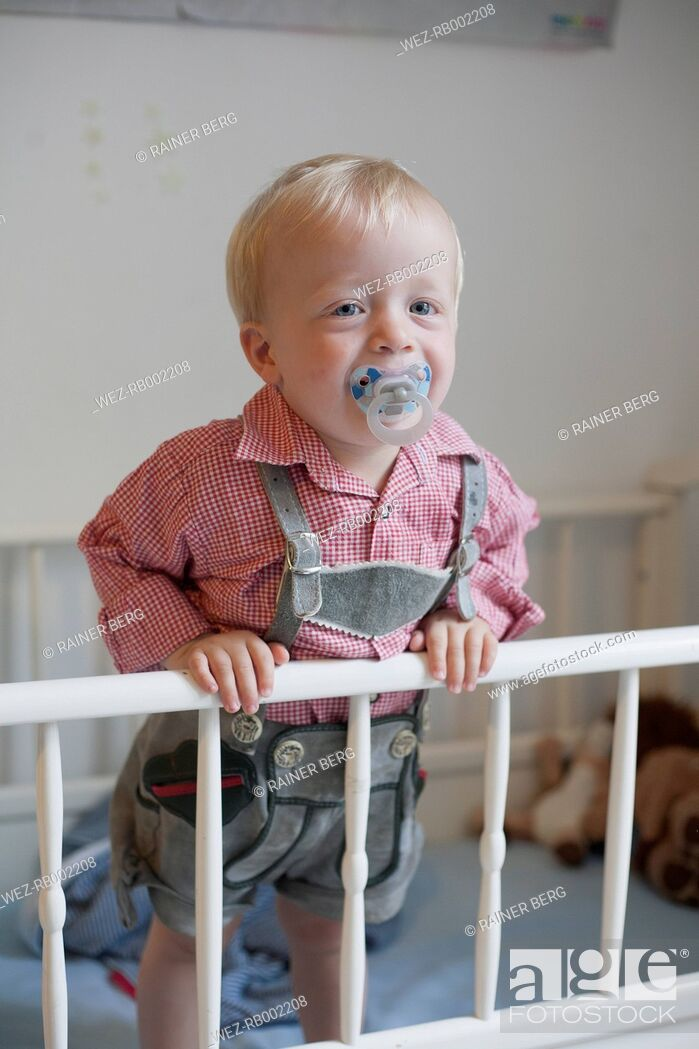 Stock Photo: Toddler with pacifier staying in his baby cot wearing traditional Bavarian leather trousers.