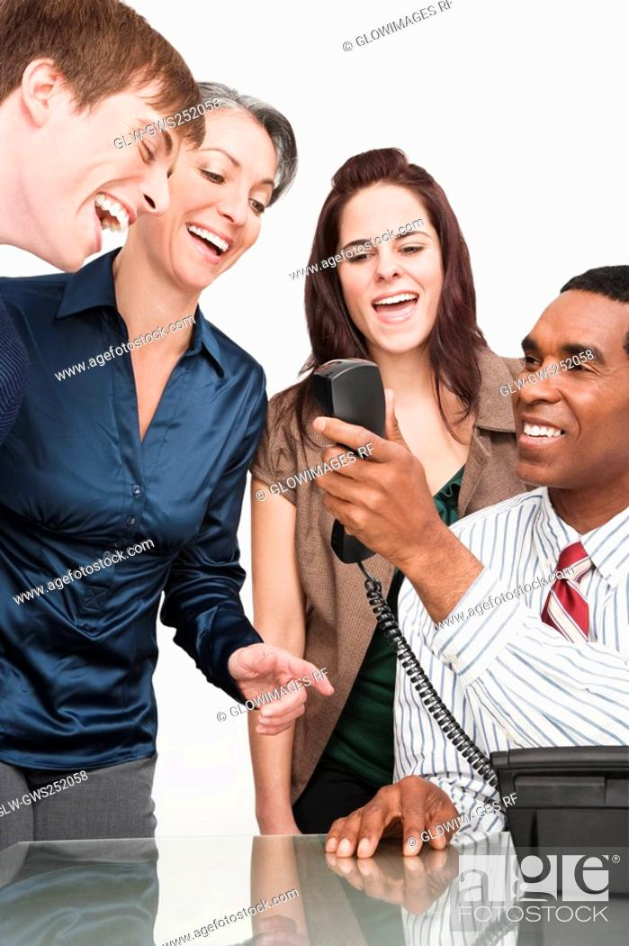Stock Photo: Businessman holding a telephone with three business executives smiling.