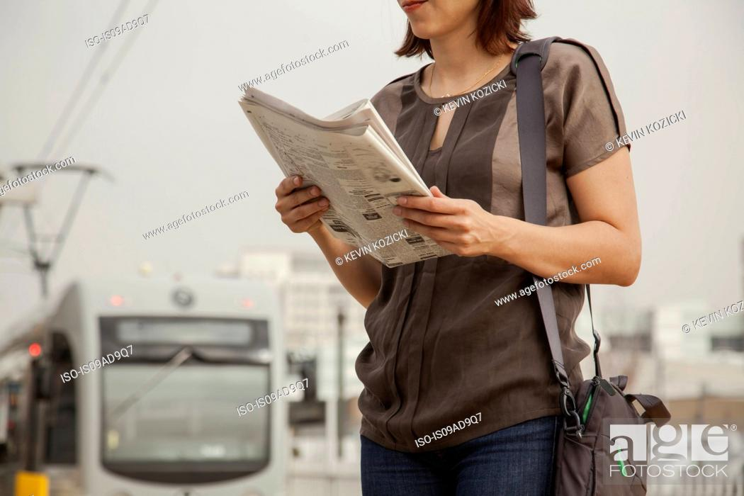 Stock Photo: Commuter reading newspaper whilst waiting at station, Los Angeles, California, USA.