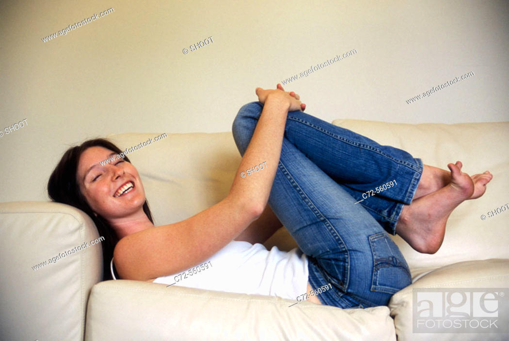 Stock Photo: Young woman lying on sofa laughing.