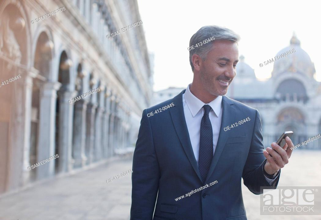 Stock Photo: Smiling businessman checking cell phone in St. Mark's Square in Venice.