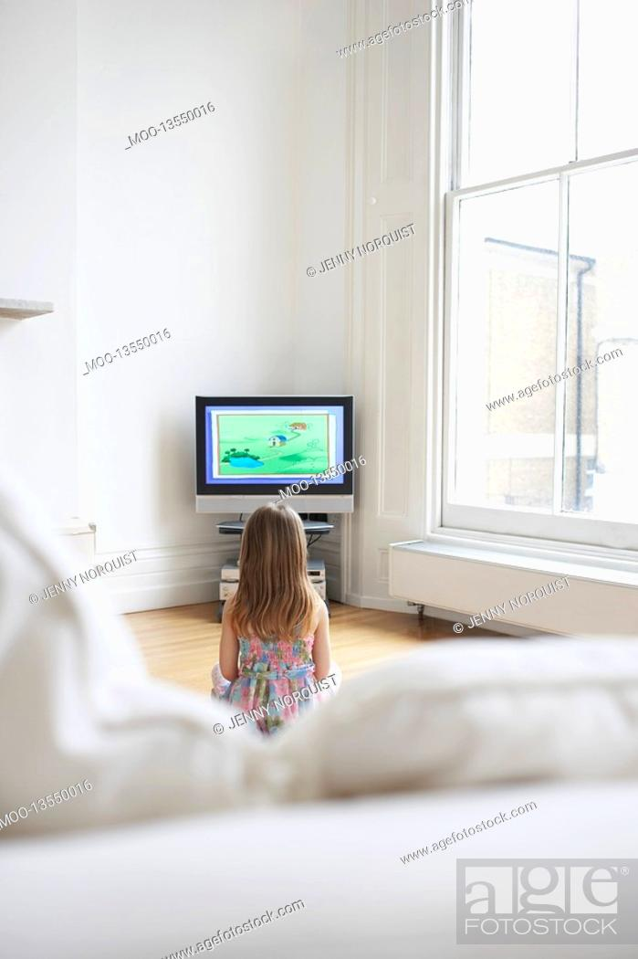 Stock Photo: Girl 5-6 watching cartoons in television back view.