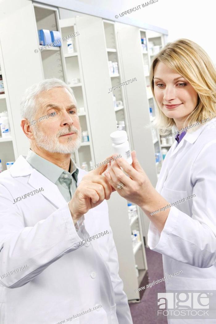 Stock Photo: Pharmacists examining label on pill bottle.