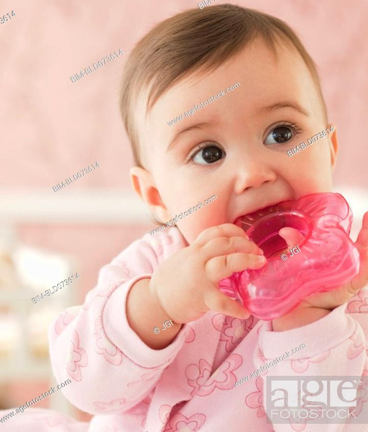 Stock Photo: Mixed race baby girl chewing on plastic toy.